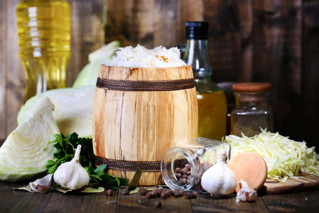 Choucroute. fresh and marinated cabbage (sauerkraut) in wooden barrel, on wooden table background